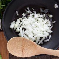 Así se hace: En una sartén ligeramente aceitada, saltear las cebollas con el azúcar, el ají molido, sal y pimienta hasta transparentar.  Cocinar las papas al horno. Reservar en un plato. Salpimentar las papas recién hechas, mezclarlas con la preparación anterior y los quesos (reservar un poco para poner encima). Distribuir en cazuelitas, cubrir con el queso restante y llevar al horno hasta gratinar. Servir enseguida.